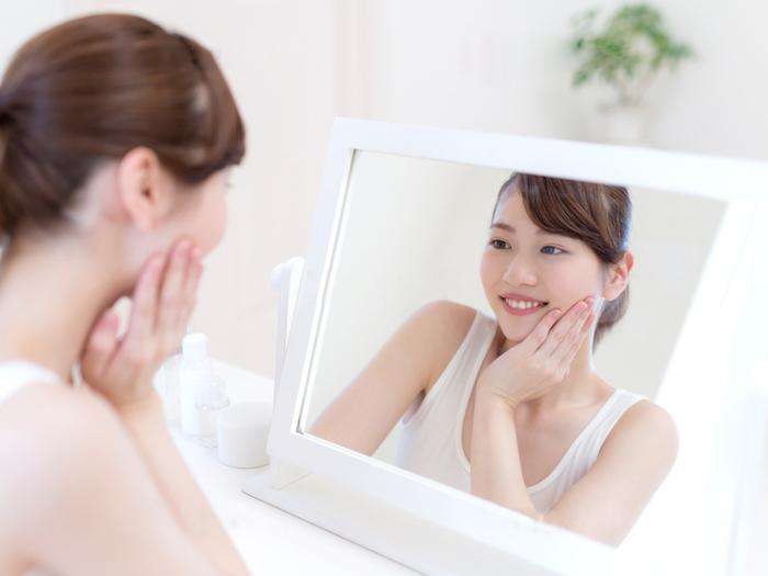 鏡で自分の肌をいる女性