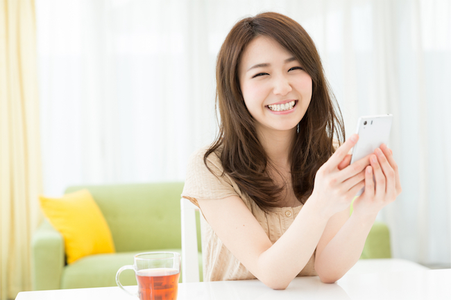 携帯を持ちながら笑顔の女性