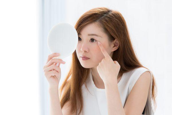 左右の目の大きさが違うメイクを鏡で確認する女性