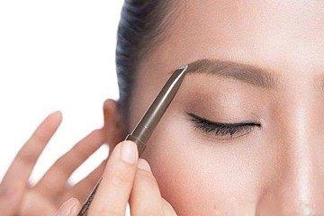 眉毛を書いている女性
