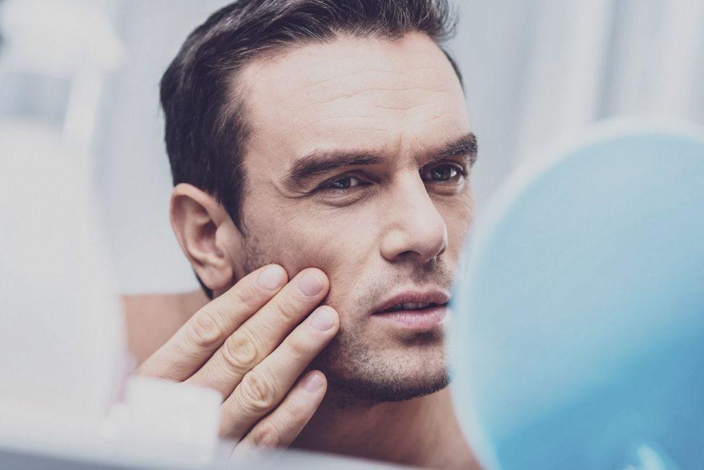 鏡で自分の肌を見る男性