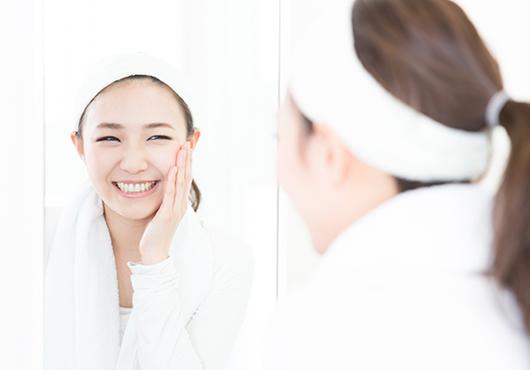 化粧を落とし、洗顔が終わった女性が鏡を見ている様子