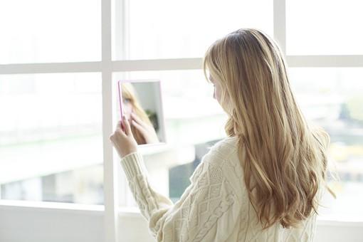 鏡えを見る女性の写真